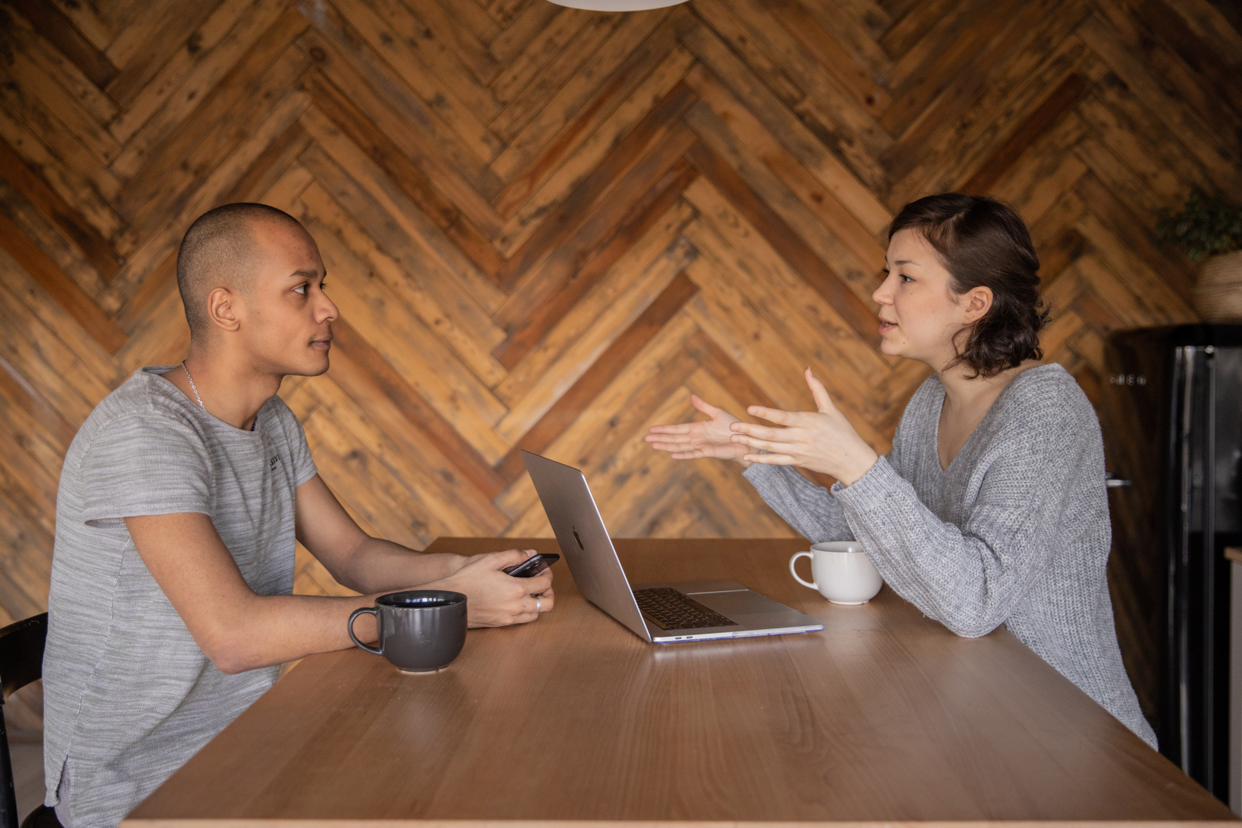 Woman from SEO agency sitting with a laptop in front of her describing a product on her business blog to a man