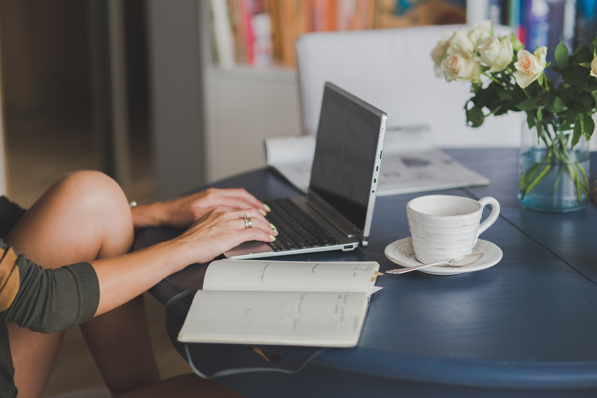 Woman sitting typing her SEO business blog on a laptop with a cup of tea and a notebook open on the table.